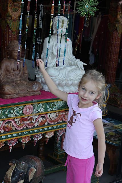 Young girl standing by statues on a table