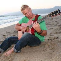 Justin James playing guitar on beach