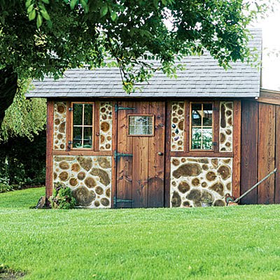 Rustic backyard shed decorated with real wood logs.
