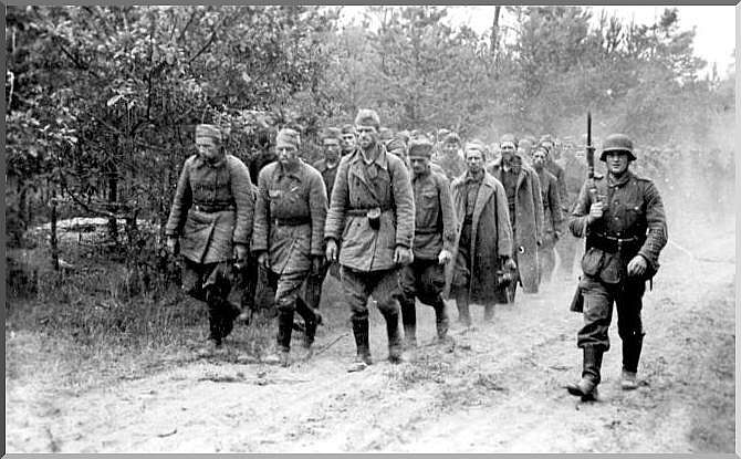 Captured soviet soldiers walk with a beady-eyed german guarding them