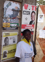 A Zimbabwean woman and campaign posters of the three presidential candidates