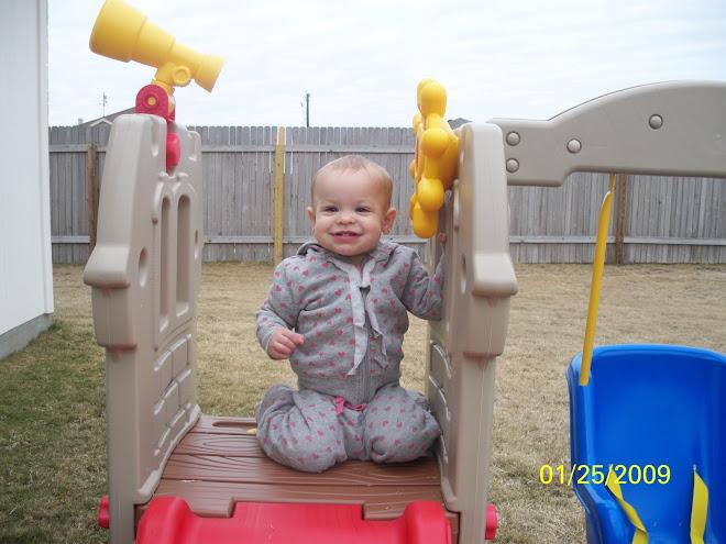 Madelyn on her swingset