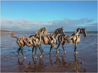 três cavalos à beira mar