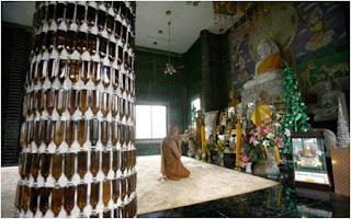Monge budista a rezar no templo feito com garrafas de vidro