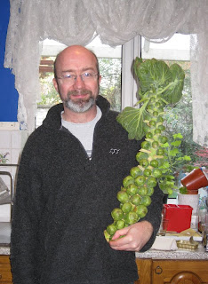 Andy holding a stalk of Brussels sprouts in the kitchen