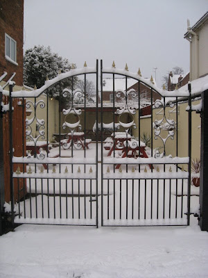 View of the snowy pub garden through the ironwork gates