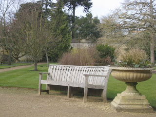 Bench in garden with stone urn