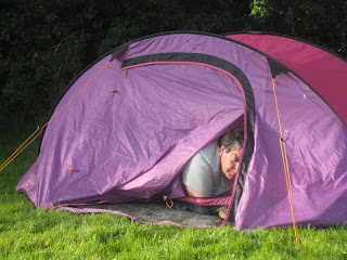 Groggy-looking man peering from the partly opened door of a bright pink tent