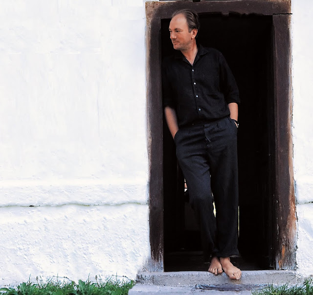 Austrian writer Thomas Bernhard stands barefoot at the door to his home