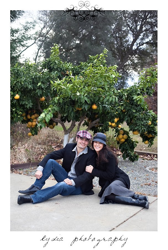 Bride and groom in front of an orange tree at lifestyle old town engagement portraits in Cottonwood, California