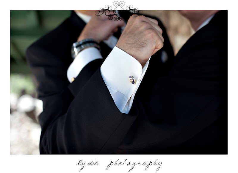 Groom and groomsman crossing arms with cufflinks at an Empire Mine State Park wedding