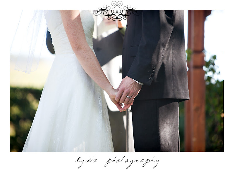 The bride and groom holding hands during their ceremony at a Kenwood Farms & Gardens wedding