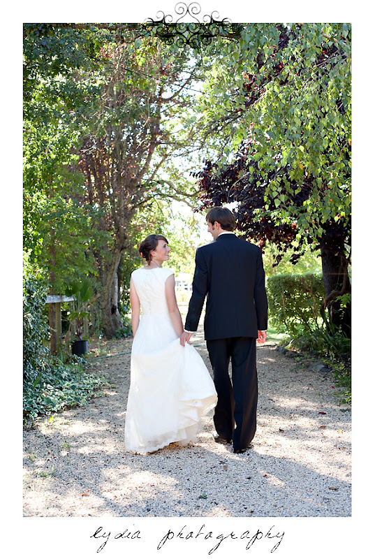 Groom holding bride's dress as they walk at a Kenwood Farms & Gardens wedding