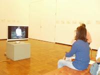 部屋中央のテレビで 田嵜さんの作品を見る。壁には立体コピー