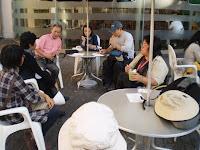 屋外のイステーブルで歓談する 田嵜さんと参加者