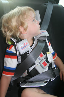 The RideSaferTM Travel Vest Restrains Childs Upper Body And Repositions Lap Belt Below Abdomen So That Organs Are Protected