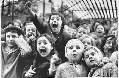 Children with various range of expressions watching story of St. George and the dragon at the puppet theater in the Tuileries.