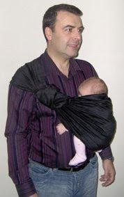Ο μπαμπάς της Ρέας, φοράει την νεογέννητη κόρη του σε ring sling έχοντας τυλίξει την ουρά γύρω απ' τους κρίκους του μάρσιπου