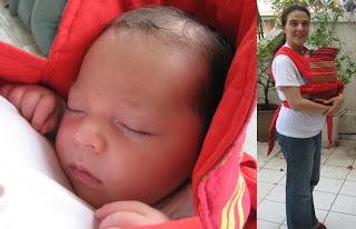 Το μωράκι κοιμάται στο mei tai στην αγκαλιά της μαμάς του