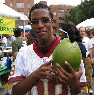 festivalgoer holding green coconut