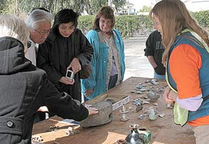 Photo of E. Gibson talking to visitors about artifacts