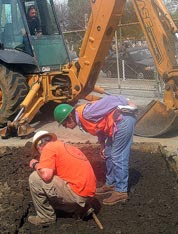 Two archaeologists checking for features in a freshly exposed surface, while the Backhoe driver looks on.