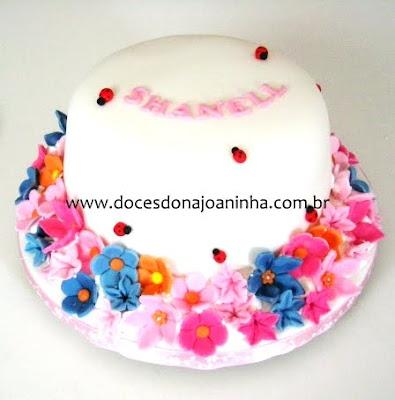 Bolo decorado com flores em rosa e lilás e mini joaninhas