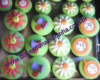 Cupcakes e mini cupcakes decorados com o o sorriso do Gato Risonho, a cartola do Chapeleiro Louco, o relógio da Lebre Maluca e flores do jardim