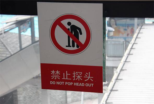 Rambu dalam bahasa inggris yang membingungkan Dilarang Menjulurkan Kepala Keluar