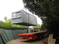 The large container being transfered from the lorry to the compound space by hiab (lorry crane)