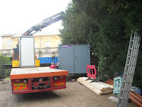 The second container being put in place - Only a portable toilet is left on the truck to be unloaded.