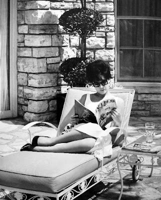 Suzanne Pleshette relaxing out by the pool with a magazine.