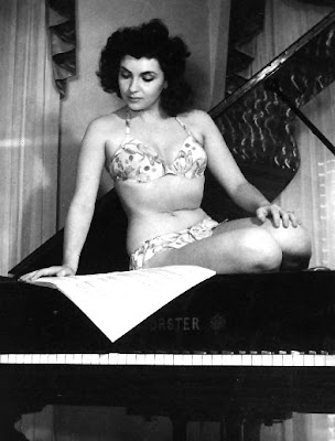 Gina Lollabrigida is reading music and not a book, but where else are you gonna find a picture of a scantily clad Gina sitting in a piano?