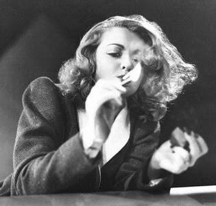 Constance Bennett fires up a Lucky Strike.