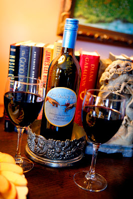 a bottle of red wine sitting on a wood table with two wine glasses in front of it and stacked books behing it