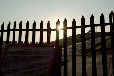 The sun peeking through the outer fence of the Agra Fort