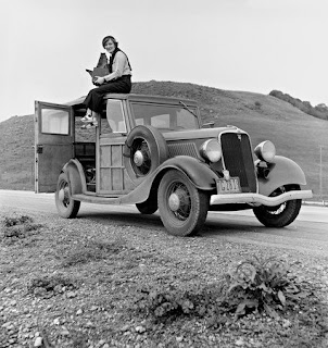 Dorothea Lange, photographer for the Farm Security Administration (FSA), sitting atop her 1933 Ford Model B, holding her camera in February 1936.