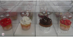 Assorted cupcake flavors topped with Venetian mask pennants and carefully placed in favor boxes
