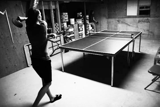 A big follow through on a ping pong swing in a Connecticut basement.