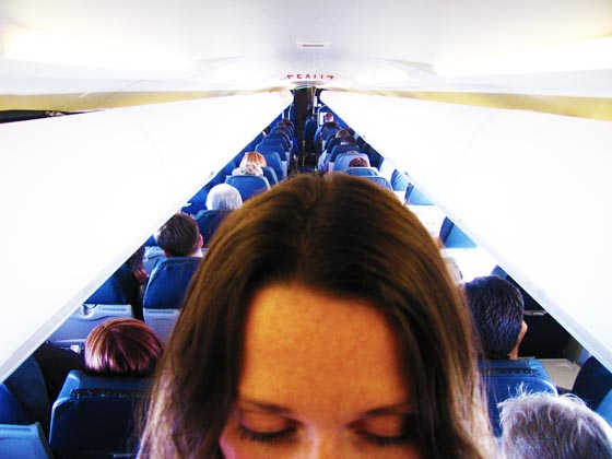 A girl standing in the aisle of a very small airplane on its way to Milwaukee, Wisconsin.