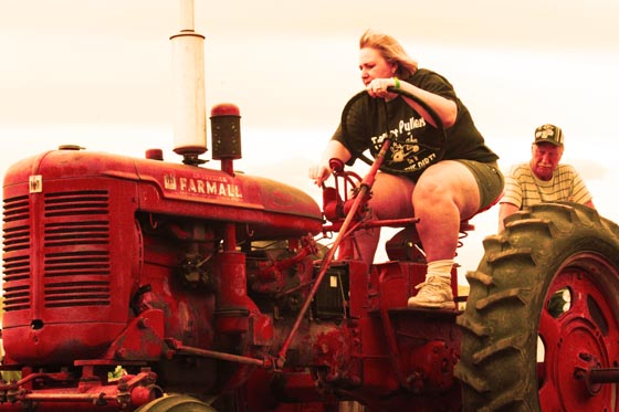 A large woman on a tractor at the Cider Days Tractor Pull in Lakewood, Colorado.