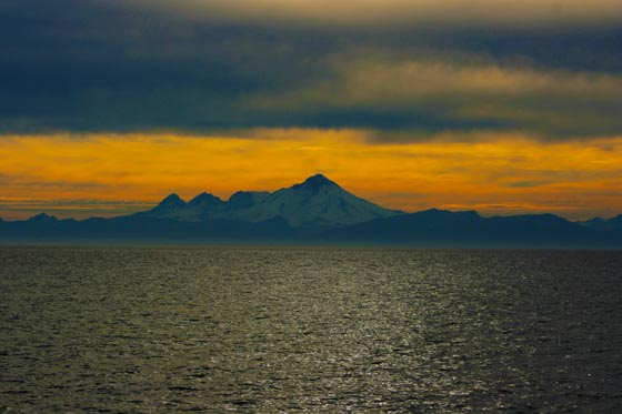 A colorful sunset behind the Redoubt Volcano from the shore in Ninilchik, Alaska.