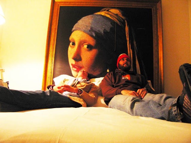 A tiny hotel room with a large Vermeer painting behind the bed at the Paramount Hotel in New York City.