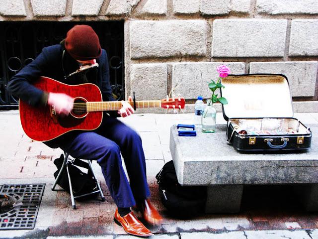 An American busker playing folk songs on a sidewalk in Madrid, Spain.