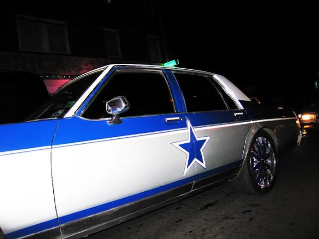 A car painted in Dallas Cowboys colors driving through Deep Ellum in Dallas,Texas.