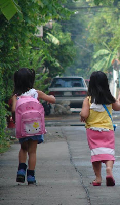 Nique (left) with her sister Nira on their way to school. Nique still has a long way to go but she definitely has the will to walk to it.