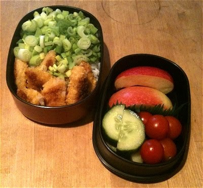 Bento mit Reis, Frühlingszwiebeln, panierten Hähnchenfilets, Apfel, Tomate und Gurke
