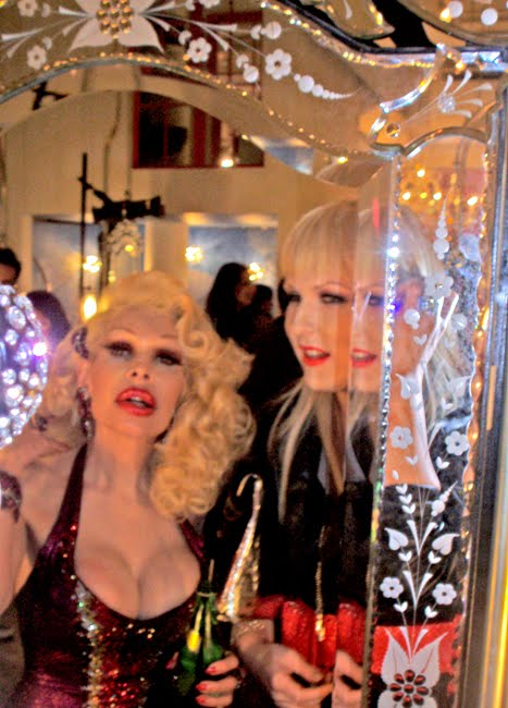 Amanda Lepore and Darian Darling touch up their makeup in a mirror at Wonderland Beauty Parlor