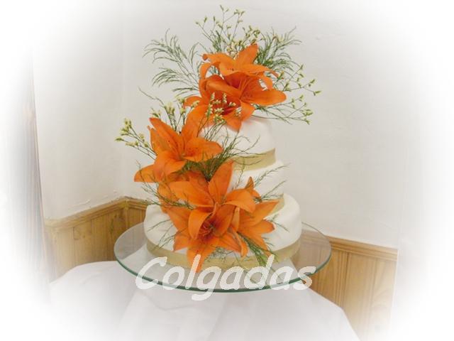 Esta torta fue decorada con flores naturales , y cintas doradas , que