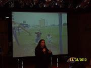 Profe Fátima falando sobre o trabalho e no telão a Paola e a Vanessa em Tramandaí.